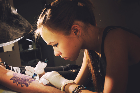 tattoo artist performing tattoo